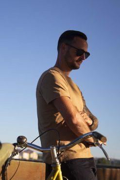 homme bras croisé avec son vélo et son t-shirt pitumarka en coton bio marron couleur naturelle - Pitumarka