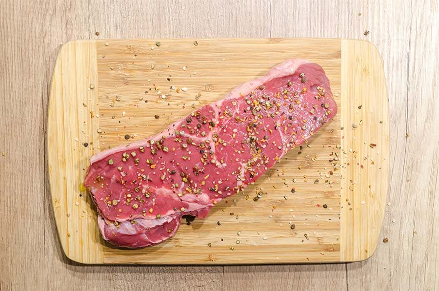 steak assaisonné sur sa planche en bois
