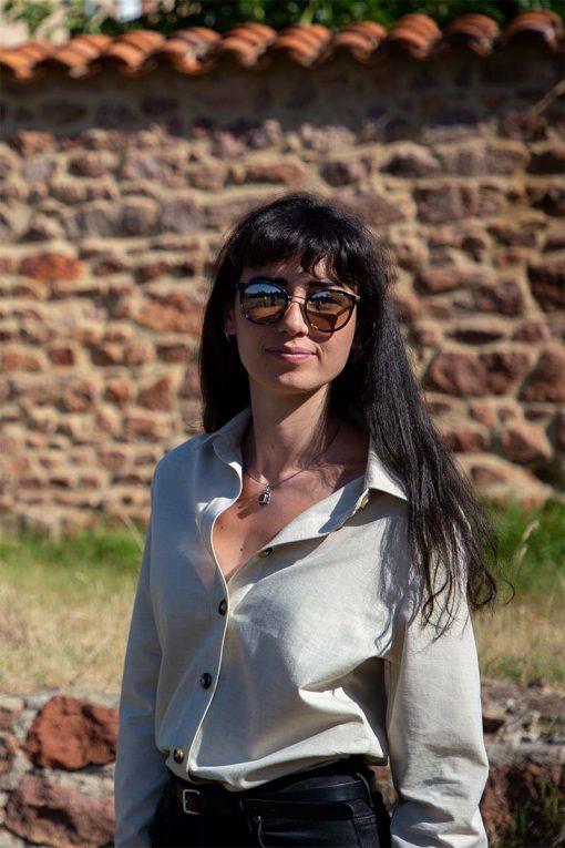 femme posant devant un mur en brique avec sa chemise avocat en coton bio pitumarka