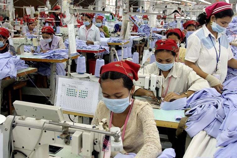 usine textile montrant des travailleurs sur leur machine à coudre