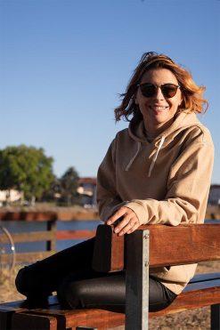 Femme assise sur un banc avec son sweat shirt Pitumarka à capuche