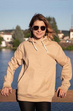 Femme adossée sur une rembarde avec son sweat shirt Pitumarka à capuche