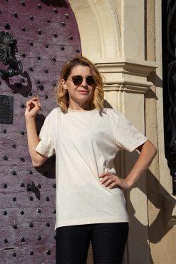 femme debout contre une porte qui porte son t-shirt en coton bio beige pitumarka